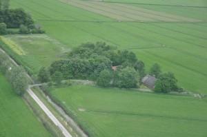 Selbst aus der Luft kaum zu erkennen: Die Reetdachkate und das Saunahaus erscheinen wie eine Insel inmitten der Wesermarsch.